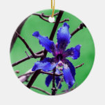 orchid colorized blue against green christmas tree ornaments