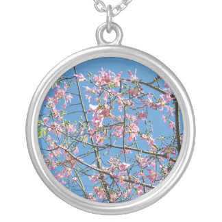 Orchid purple tree against bright blue sky round pendant necklace