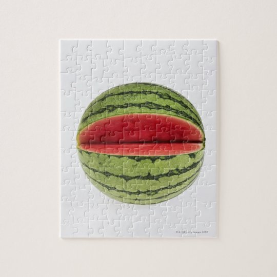 Organic watermelon with a slice cut into it, on jigsaw puzzle