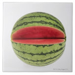 Organic watermelon with a slice cut into it, on ceramic tiles