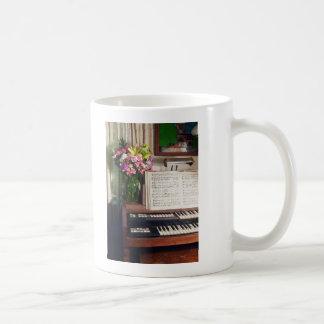 Órgano con el ramo de flores tazas de café