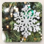 Ornamento brillante del copo de nieve en el árbol  posavasos