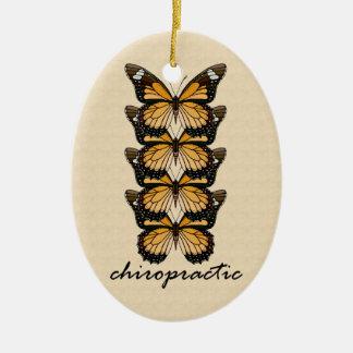 Ornamento de las mariposas de la quiropráctica adorno navideño ovalado de cerámica