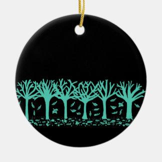 Ornamento hivernal de la silueta de los árboles y adorno navideño redondo de cerámica