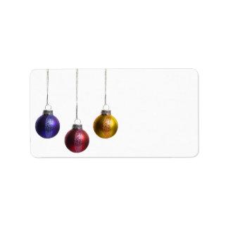 Ornamentos del navidad en oro verde rojo púrpura d etiqueta de dirección