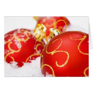 Ornamentos rojos del árbol de navidad tarjeta de felicitación