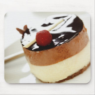 Ornate cheesecake on plate with coffee cup in mouse pad