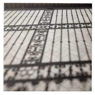 ornate iron fencing shadow on tile floor