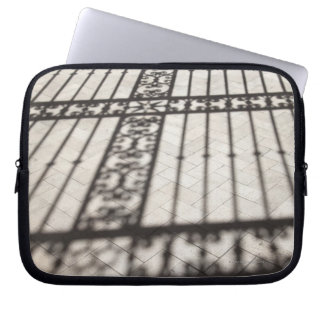 ornate iron fencing shadow on tile floor laptop sleeve