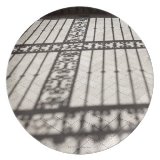 ornate iron fencing shadow on tile floor plate
