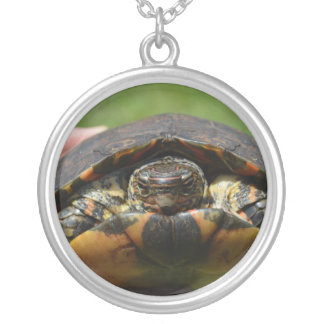Ornate wood turtle in hand round pendant necklace