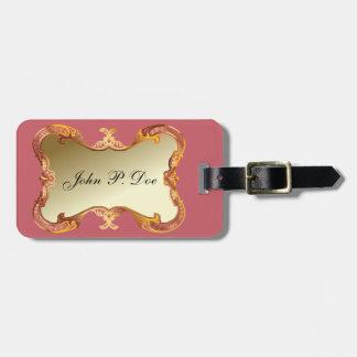 Oro con monograma y etiqueta rosada del equipaje