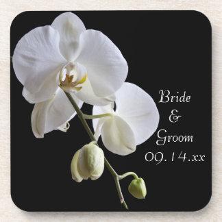 Orquídea en los prácticos de costa negros del corc posavasos de bebidas