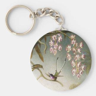 Orquídeas del aerosol con el llavero del colibrí
