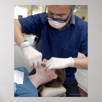 Orthodontist que reajusta los apoyos dentales de a poster