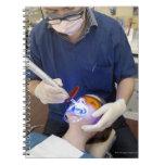 Orthodontist que usa la luz UV para fijar el hormi Cuaderno