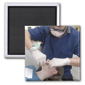 Orthodontist readjusting the dental braces of a magnet