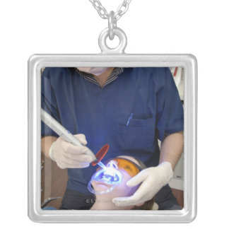 Orthodontist using UV light to set the concrete Silver Plated Necklace