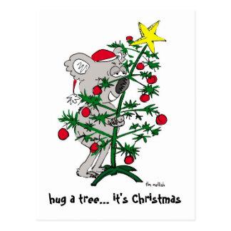 Oso de koala que abraza un árbol de navidad postales