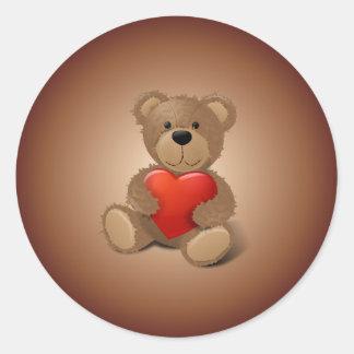 Oso de peluche con el corazón de la tarjeta del pegatina redonda
