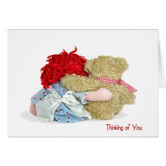 Oso de peluche y muñeca de trapo que piensa en tarjeta de felicitación
