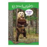 Oso divertido en las maderas con la torta de tarjeta de felicitación