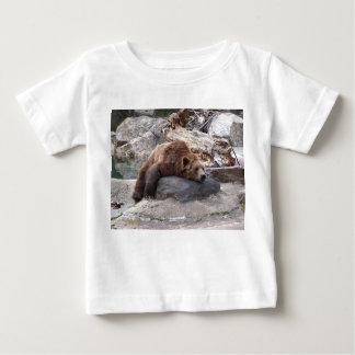 Oso grizzly que descansa sobre roca playera de bebé