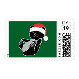 Oso negro del navidad con el gorra rojo de Santa Sellos Postales