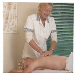 Osteopath/chiropractor manipulating back large square tile