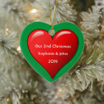 """Our Second Christmas Together Cute Red Heart 2019 Ceramic Ornament<br><div class=""""desc"""">Personalized names and printed with cute red heart design in solid green background. Feel free to customize by adding your own texts,  names or photos. You can add your photo on the back side of the ornament easily! The color of the background can also be changed as you want.</div>"""
