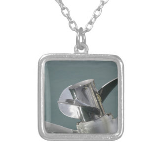 Outboard boat motor tuned up on sea background silver plated necklace
