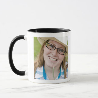 Outdoor portrait of smiling cowgirl biting grass mug