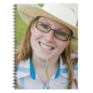 Outdoor portrait of smiling cowgirl biting grass notebook