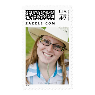 Outdoor portrait of smiling cowgirl biting grass postage
