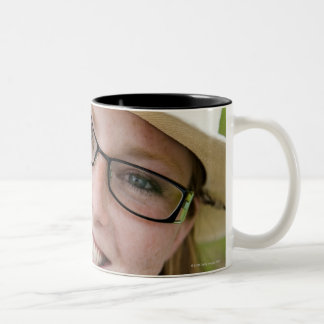 Outdoor portrait of smiling cowgirl biting grass Two-Tone coffee mug