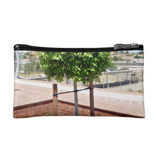 Outdoor topiary in brick planter makeup bags