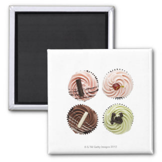 Overhead view of four cup cakes on white magnet