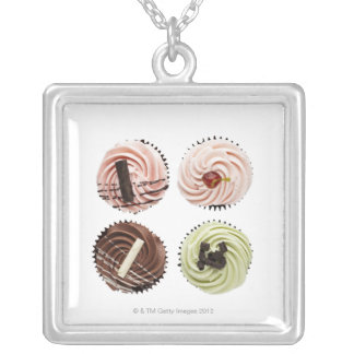 Overhead view of four cup cakes on white silver plated necklace