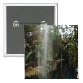 Overhead waterfall flows down into a pool of water pinback button