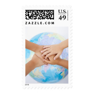 Overlapping hands and a globe postage