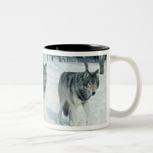 Pack of wolves at edge of snowy forest Two-Tone coffee mug