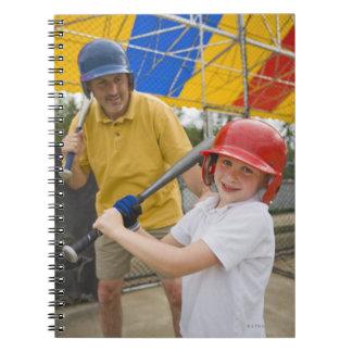 Padre con la hija en la jaula de bateo libretas