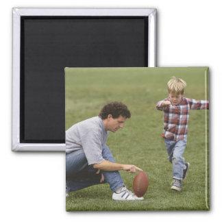 Padre e hijo (4-6) que juegan a fútbol americano imán cuadrado