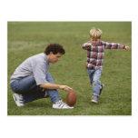 Padre e hijo (4-6) que juegan a fútbol americano postal