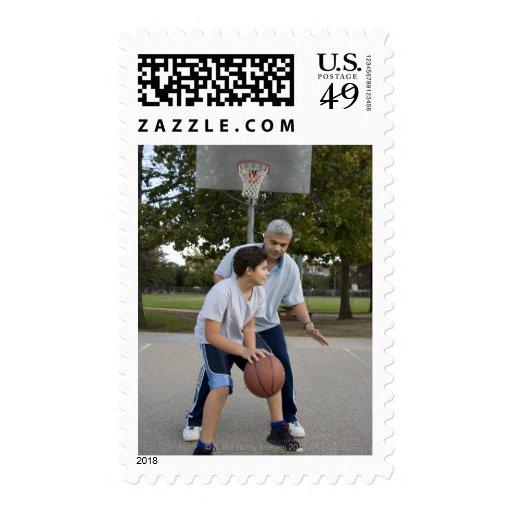 Padre hispánico e hijo que juegan a baloncesto franqueo