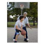 Padre hispánico e hijo que juegan a baloncesto postal