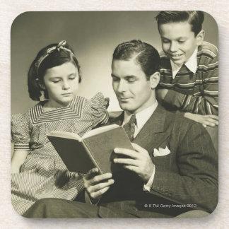 Padre que lee al hijo posavasos de bebida