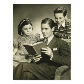 Padre que lee al hijo postales
