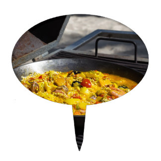 Paella is cooked on a grill cake topper