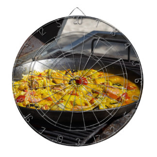 Paella is cooked on a grill dartboards